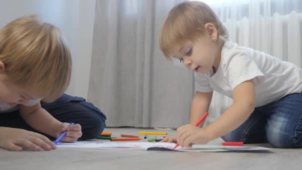 děti kreslí s plstěnými pery na albu. malý chlapec a dívka koncept dětství bratr a sestra hrát barvu na podlaze s barevnými markery životní styl