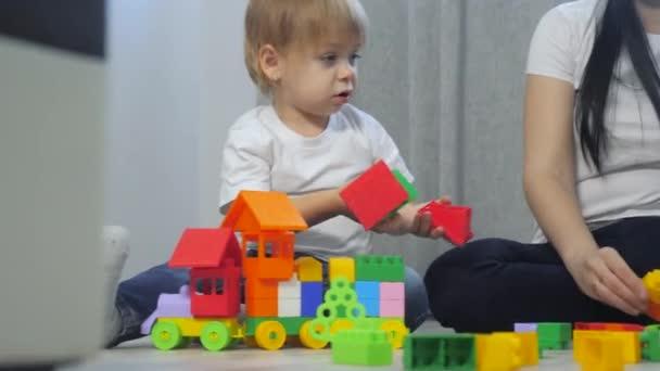dětství šťastná rodina maminka a děti hrají koncept holčička a chlapec bratr a sestra sbírá konstruktér týmová práce. dítě hraje hračky sedící na podlaze. děti si hrají v týmových hračkách na podlaze