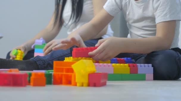 gyermekkori boldog család anya és gyerekek játszanak koncepció kislány és fiú testvér életmód gyűjti építész csapatmunka. A gyerek játékokat játszik a padlón. a gyerekek csapatjátékokban játszanak