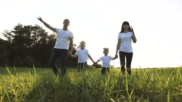 happy family teamwork daddy mother, little brother and sister walk in the park nature holding hands slow motion video concept. father mom, kids lifestyle boy and girl daughter and son hold hands go on