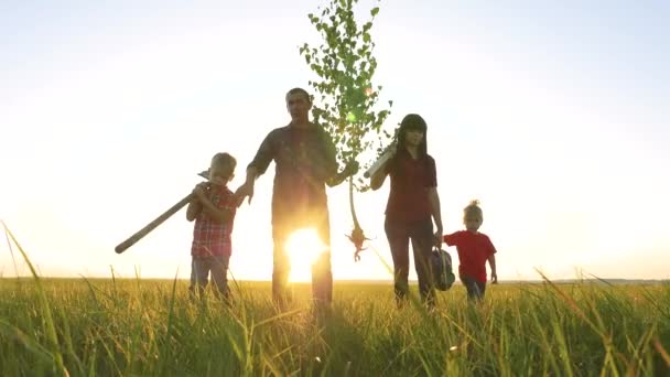 agriculture red neck farming happy family walking agriculture of farmers a silhouette concept slow motion video. mom lifestyle dad son and daughter walk go children happy family plant and water the