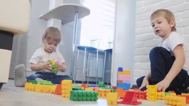 Dětství šťastný rodinný koncept holčička a chlapec bratr a sestra sbírá konstruktér týmová práce. dítě hraje hračky sedící na podlaze. děti životní styl hrát v týmu hračky na podlaze v místnosti