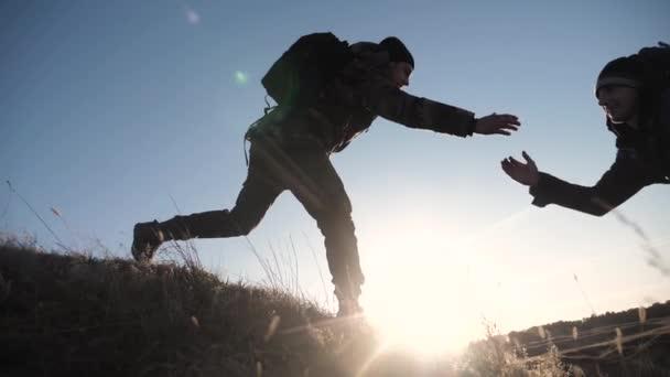 Teamwork zwei Männer helfen bei der Hand Business-Reise Silhouette Konzept. Zwei Touristen helfen beim Besteigen der Felswände. Bergsteiger klettern an die Spitze Teamwork überwindet Strapazen die