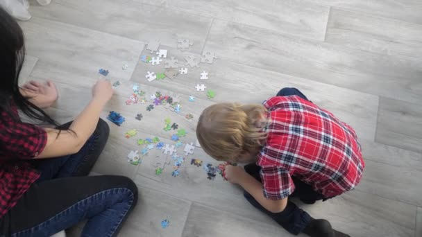 happy family lifestyle collection puzzles teamwork. development of fine motor skills and thinking. little son boy a and girl mom collect mosaic puzzles