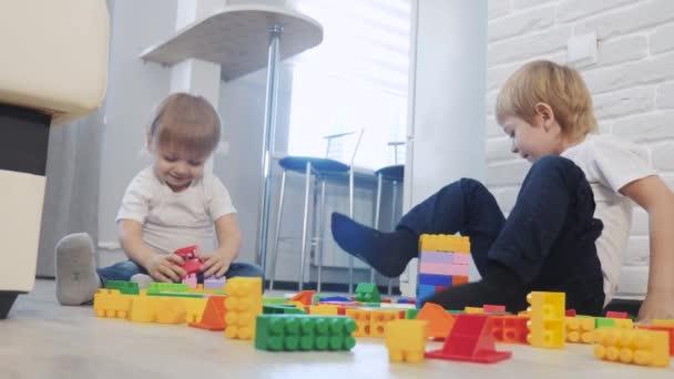 Dětství šťastný rodinný koncept holčička a chlapec bratr a sestra sbírá konstruktér týmová práce. dítě hraje hračky sedící na podlaze. děti hrát v životním stylu týmové hračky na podlaze v místnosti