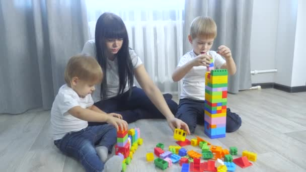 childhood happy family mom and children are playing concept little girl and boy brother and sister collects constructor teamwork. child plays lifestyle toys sitting on floor. children play in a team