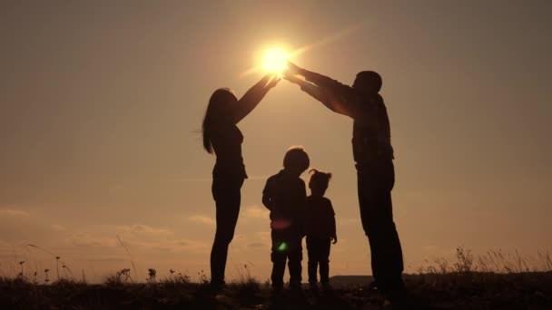 happy family teamwork silhouette shows a house and comfort symbol at sunset. mom dad and kids children portray a house roof hold their hands lifestyle over their heads