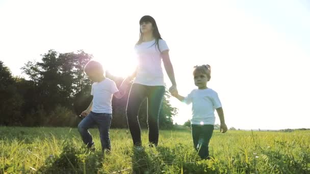 happy family teamwork mother, little brother and sister walk in the park nature holding hands slow motion video concept. mom, kids boy and girl daughter lifestyle and son hold hands go on green grass