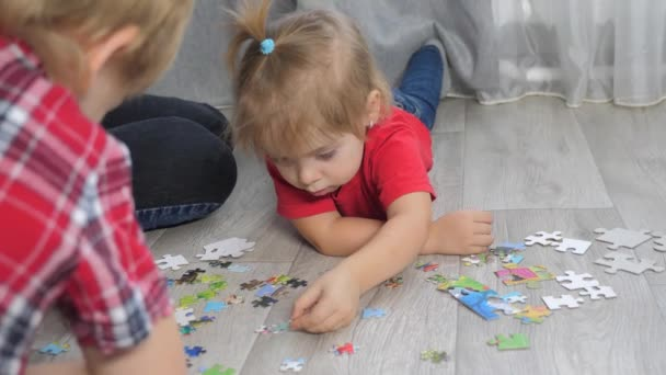 little daughter girl happy family collection puzzles teamwork. development of fine motor skills and thinking. daughter and girl with mom a collect mosaic puzzles lifestyle