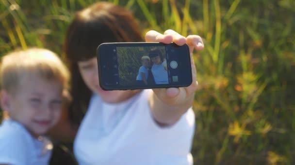Máma a malý syn malý chlapec vzít selfie na smartphone na přírodním pojetí šťastný rodinný týmová práce. mateřství a rodičovství matka fotí pro rodinný archiv. šťastný přátelský rodina maminka a