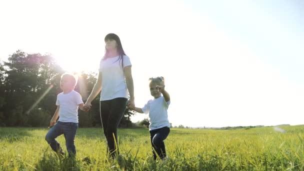 šťastná rodinná týmová práce matka, mladší bratr a sestra procházka v parku příroda drží ruce zpomalené video koncept. Máma, děti chlapec životní styl a dívka dcera a syn držet ruce jít na zelené trávě