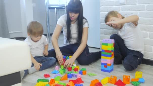 dětství šťastná rodina maminka a děti hrají koncept holčička a chlapec bratr a sestra sbírá konstruktér týmová práce. dítě hraje hračky sedící na podlaze. děti si hrají v životním stylu a týmu