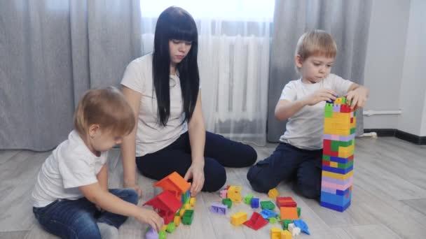 dětství šťastná rodina maminka a děti hrají koncept holčička a chlapec bratr a sestra sbírá životní styl konstruktér týmová práce. dítě hraje hračky sedící na podlaze. děti si hrají v týmu