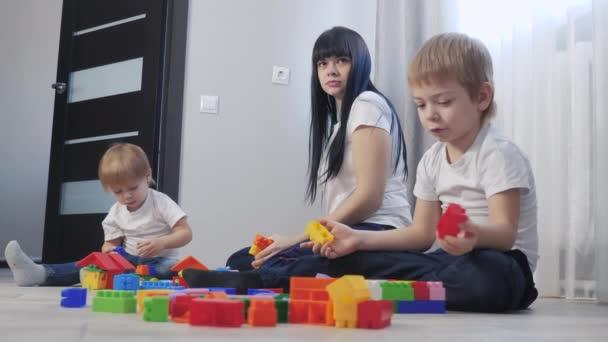 dětství šťastná rodina maminka a děti hrají koncept holčička a chlapec bratr a sestra sbírá konstruktér týmová práce. dítě si hraje s hračkami. děti životní styl hrát v týmu hračky