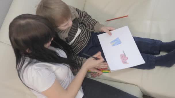 malý chlapec a máma kreslit týmovou práci životní styl šťastný rodinný koncept. Dítě syn s matkou žena jsou zapojeny do kreslení tužkou. lekce s dětským rozvojem tvořivosti