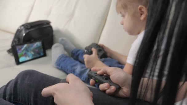 matka a životní styl děti hrají konzoli v gamepads týmové práci. Máma a děti, kluk a holka hrajou přenosnou set-top krabici v TV řadiči. šťastný rodina malý chlapec a dívka mají online zábavu