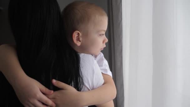 Máma drží svého syna v náručí. šťastný rodinný koncept. Máma drží trochu životního stylu chlapce v náručí při pohledu z okna vnitřní péče o dítě šťastná rodina