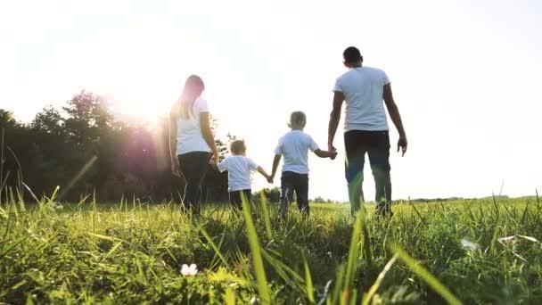 šťastná rodinná týmová práce tatínek maminka, mladší bratr a sestra procházka v parku příroda drží ruce zpomalené video koncept. otec maminka, děti chlapec a dívka dcera a syn držet ruce jít na zelenou