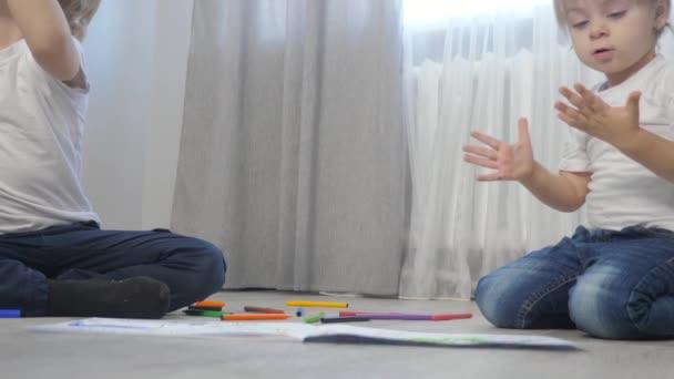 děti kreslí s plstěnými pery na albu. malý chlapec a dívka koncept dětství bratr a sestra hrát barvu na podlaze životní styl s barevnými markery