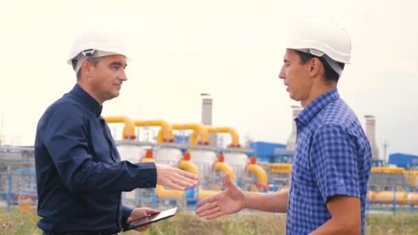 Dva muži si potřásají rukou a pracují jako inženýři v plynárně vyrábějící plynový olej. handshake kontrakt průmysl obchodní týmová práce koncept. Pracovník a inženýr studovat plán výroby životního stylu plynu