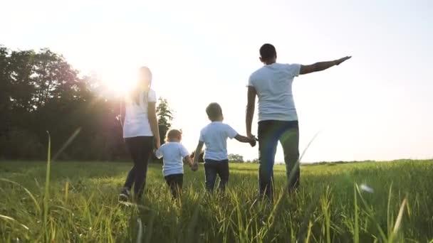 šťastná rodinná týmová práce tatínek maminka, mladší bratr a sestra procházka v parku příroda drží ruce zpomalené video koncept. otec maminka, děti chlapec a dívka dcera a syn držet životní styl ruce jít na