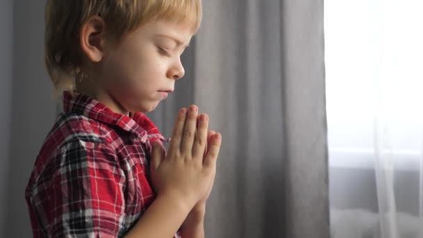 kleiner Sohn Junge betet vor dem Schlafengehen Religion Konzept Lebensstil. Gebetskind im Haus betet am Bett vor dem Fenster