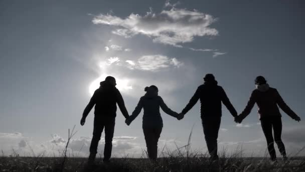 happy family and dog silhouette walking at sunset teamwork. group of people friends walking holding hands slow motion video. Happy family party and pet lifestyle teamwork concept