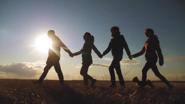 happy lifestyle family and dog silhouette walking at sunset teamwork. group of people friends walking holding hands slow motion video. Teamwork happy family party and pet concept