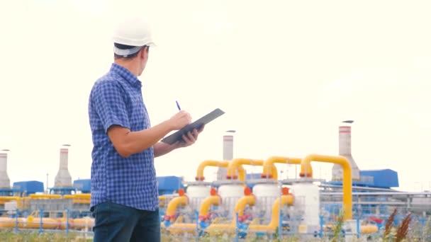 Konzept für die Förderung von Erdöl und Erdgas im Bergbau. Ingenieurskraft und Energie mittels digitaler Tablets. Arbeiter mit Helm arbeitet in einer Öl- und Gasanlage. Ingenieur-Studium dokumentiert Wirtschaftsbranche