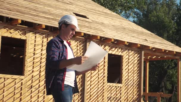 concept building constructing architect slow motion video. man builder in a helmet stands at construction holding a lifestyle scheme house plan. site near a wooden frame house under construction
