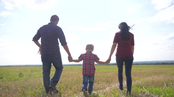 životní styl šťastný rodina chůze příroda týmová práce přátelství péče koncept zpomalení videa. otec maminka a syn procházka v přírodě západ slunce slunce držet za ruku. šťastný rodina rodiče muž a dívka držet malý chlapec