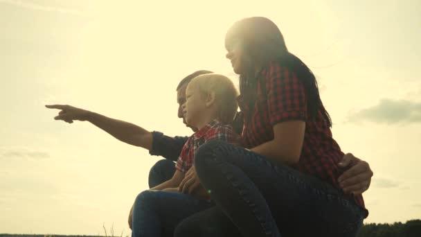 šťastná rodinná týmová práce koncept zpomalení videa. táta a syn silueta sedí venku před západem slunce. otec muž objetí maminka dívka a syn ukazuje ruce životní styl v dálce šťastná rodina