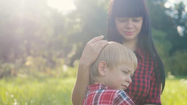 šťastný rodinný koncept matky a syna. Máma něžné dětství video životní styl. zpomalit video.maminka brunetka dívka jemně objímá a stará se o chlapce syn blondýny venku