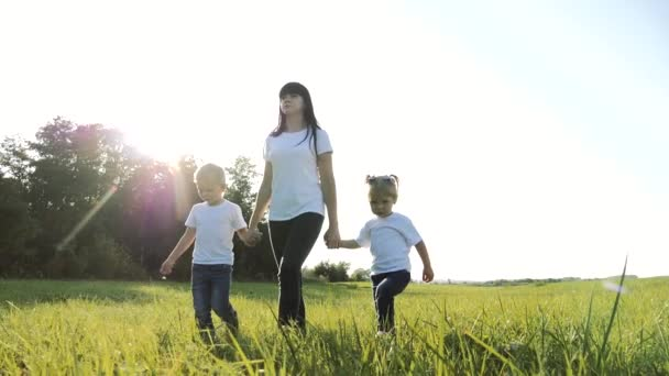 happy family teamwork mother, little brother and sister walk in the park nature holding hands slow motion video concept. mom, kids lifestyle boy and girl daughter and son hold hands go on green grass