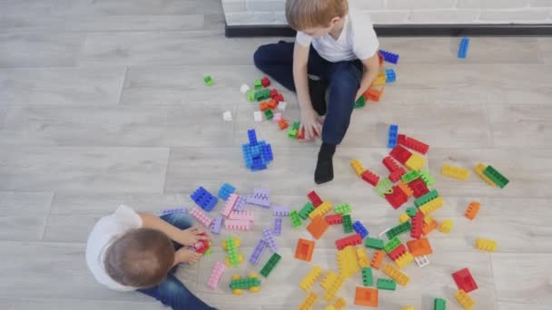 childhood happy family concept little girl and boy brother and sister collects constructor lifestyle teamwork. child plays toys sitting on the floor. children play in a team toys on floor in the room