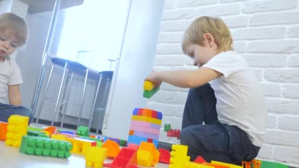 Dětství šťastný rodinný koncept holčička a chlapec bratr a sestra sbírá konstruktér týmová práce. dítě hraje životní styl hračky sedí na podlaze. děti si hrají v týmu hraček na podlaze v místnosti