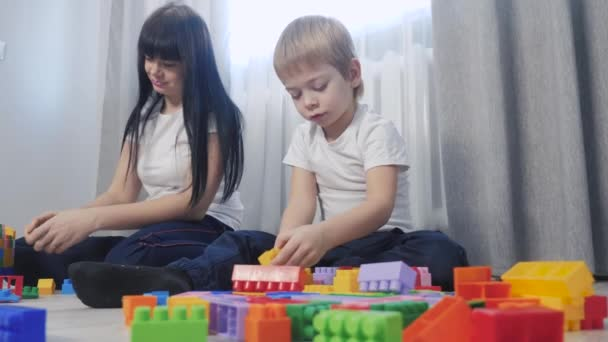 childhood lifestyle happy family mom and children are playing concept little girl and boy brother and sister collects constructor teamwork. child plays toys sitting on floor. children play in team