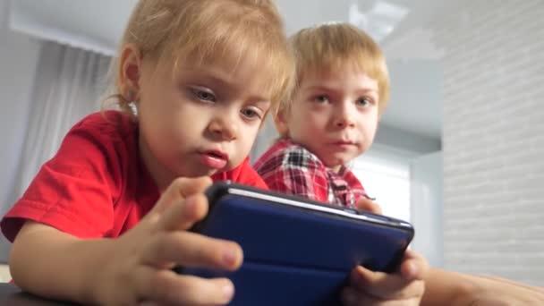Kinder schauen sich Online-Video-Cartoons auf dem Smartphone an. Kinder kleiner Junge und Mädchen Bruder Schwester Lifestyle ansehen Online-Streaming-Übertragung des Telefons