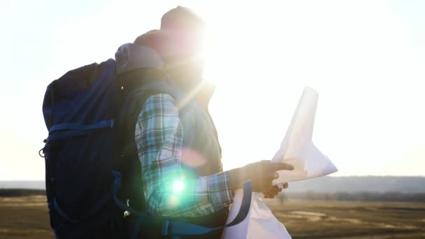 tourist traveler man with paper map a navigating looking search path on map. business concept freedom lifestyle travel tourism adventure. Hipster silhouette sunlight tourist with backpack