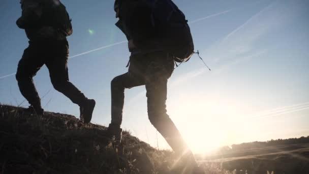 dva turisté týmová práce s batohy životní styl zpomalení chůze jít silueta ve slunečním světle záře slunce při západu slunce. dva muži turisté vylézt hory překonávání obtíží koncept týmová práce