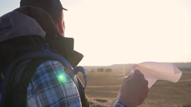 turistický cestovatel muž s papírovou mapou životní styl navigační hledá cestu na mapě. podnikatelský koncept svoboda cestování turistika dobrodružství. Hipster silueta slunce turista s batohem