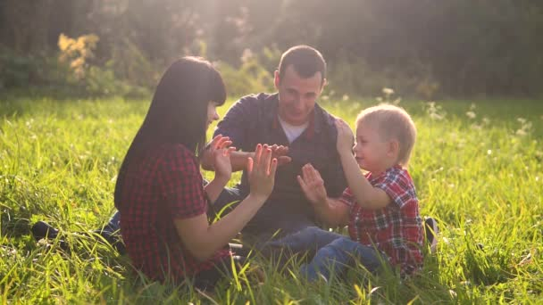 šťastný rodinný životní styl týmová práce venku koncept venku zpomalení videa. Máma táta a syn v přírodě sedí na trávě a baví se. hrát maminka dívka táta muž a syn chlapec šťastný rodina