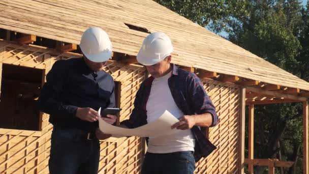 Csapatmunka. koncepcióépítés építész lassított felvételeket készít. Két sisakos férfi tanulmányozza a ház tervét. két építész dolgozik az építési keret ház üzleti kontraszt a