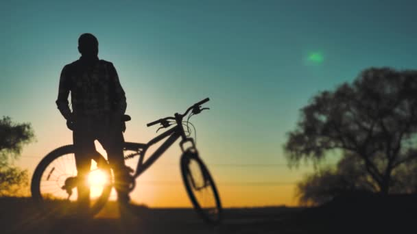 silhouette the man and a bicycle on sunset background. exercise healthy lifestyle movement. man with a backpack at sunset on a bicycle stands looking lifestyle into the distance