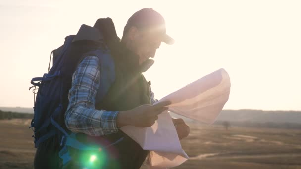tourist traveler man with paper map a navigating looking search path on map. business concept freedom travel tourism adventure. Hipster silhouette sunlight tourist with backpack lifestyle