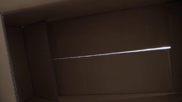 Chlapec otevře balíček s překvapením. kluk otevře kartónovou krabici a bude vypadat jako dárek. dětský životní styl vypadá v krabici je šťastný údiv