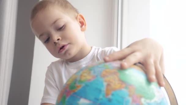 fiú tanul földgömb. oktatás életmód utazási turizmus koncepció. gyermek csavarja a földgömb ül egy ablakpárkányon. A kölyök egy országot keres egy földgömb térképen. világtérkép földrajz tanulmány