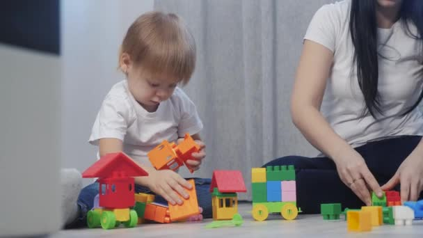 childhood happy family mom and children are playing concept little girl and boy brother and sister collects constructor teamwork. child plays toys sitting on floor. children lifestyle play in team