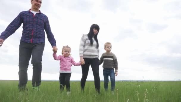 glücklicher Lebensstil der Familie. Mama Papa und kleine Kinder spazieren im Park im Freien und halten Händchen. Frau, Mann, kleiner Junge und Mädchen bei Sonnenuntergang auf der grünen Wiese