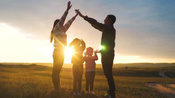 happy family. teamwork adult parents and small children shows a house and comfort symbol silhouette at sunset. lifestyle happy family mom dad and kids children portray a house roof hold their hands